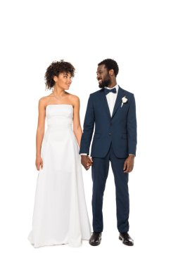 Cheerful african american bride and bridegroom holding hands while standing isolated on white stock vector