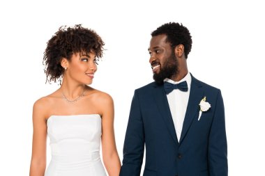 Happy african american bride and bridegroom looking at each other isolated on white stock vector