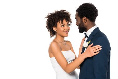 Cheerful african american bridegroom looking at bride while hugging isolated on white stock vector