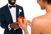 oříznutý pohled na šťastného afroamerického ženicha, který dává dárek nevěstě nevěstu izolaci na bílém