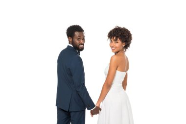 Positive african american bridegroom and bride standing and holding hands isolated on white stock vector