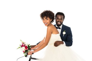 Cheerful african american bridegroom near attractive bride riding bicycle isolated on white stock vector