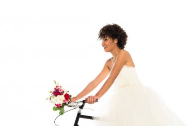 Low angle view of attractive african american bride in wedding dress holding flowers while riding bicycle isolated on white stock vector