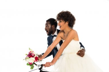 Surprised african american bridegroom near happy bride with flowers riding bicycle isolated on white stock vector