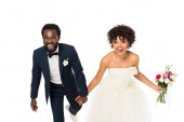 happy african american bride in wedding dress holding hands with bridegroom isolated on white