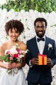fröhliche afrikanisch-amerikanische Braut mit Blumen in der Nähe des Bräutigams mit Geschenk