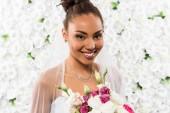 vidám afro-amerikai menyasszony fátylat gazdaság csokor virág