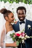 boldog afro-amerikai menyasszony, fehér fátyol mosolyogva közelében vőlegény és virágok