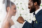 happy african american bridegroom touching white veil and smiling near bride and flowers