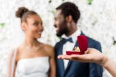 selective focus of man holding box with wedding ring near african american couple