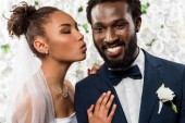 african american bride in veil with duck face near happy bridegroom and flowers