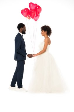 Side view of cheerful african american bridegroom holding hands with attractive bride near balloons isolated on white stock vector