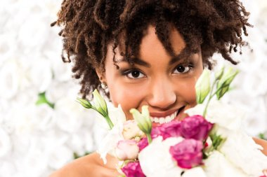 Selective focus of cheerful african american bride looking at camera while holding flowers stock vector