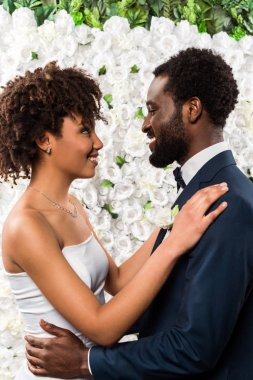 Happy african american bride hugging handsome bearded bridegroom near flowers stock vector