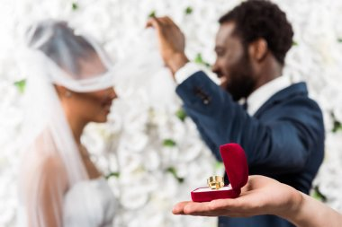 cropped view of man holding box with wedding ring near african american couple