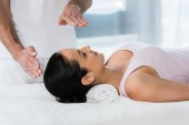 Photo cropped view of healer putting hands above head of brunette girl on massage table