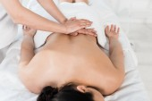 cropped view of masseur doing massage to woman in spa center
