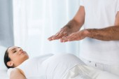 Photo selective focus of man healing brunette pregnant woman lying on massage table