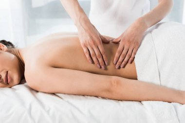 cropped view of masseur doing massage to woman lying on massage table