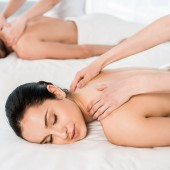 selective focus of masseur doing massage to attractive woman with closed eyes near man
