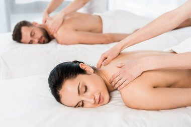 selective focus of masseur doing massage to woman with closed eyes near man in spa center