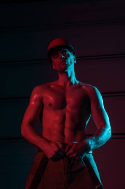 sexy shirtless fireman in protective hardhat in darkness