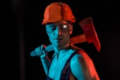 shirtless fireman in overall, hardhat and protective goggles holding flat head axe on black