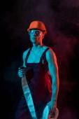 sexy hasiče v tvrdých a ochranných brýlí, které drží požární hadici v kouřových kouři na černém