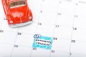auto s červeným hračkou v kalendáři s vyznačeným datem