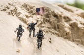 vojáci hraček se zbraněmi stojící na písku a držící americkou vlajku
