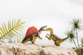 Photo selective focus of toy dinosaurs roaring on sand dune with exotic leaves