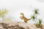 Photo selective focus of toy dinosaur on sand dune with tropical leaves