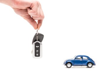 Cropped view of man holding key near toy car on white stock vector