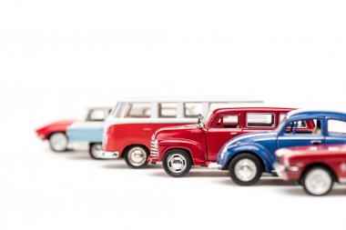 Selective focus of colorful toy cars and bus on white stock vector