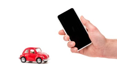 Cropped view of man holding smartphone with blank screen and red toy car on white stock vector