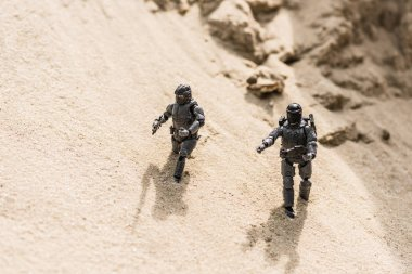 Tiny toy soldiers on sand with shadows in daylight stock vector