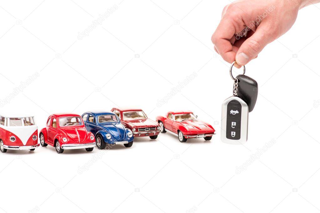 vista ritagliata di uomo in possesso di chiavi e auto giocattolo colorato su bianco