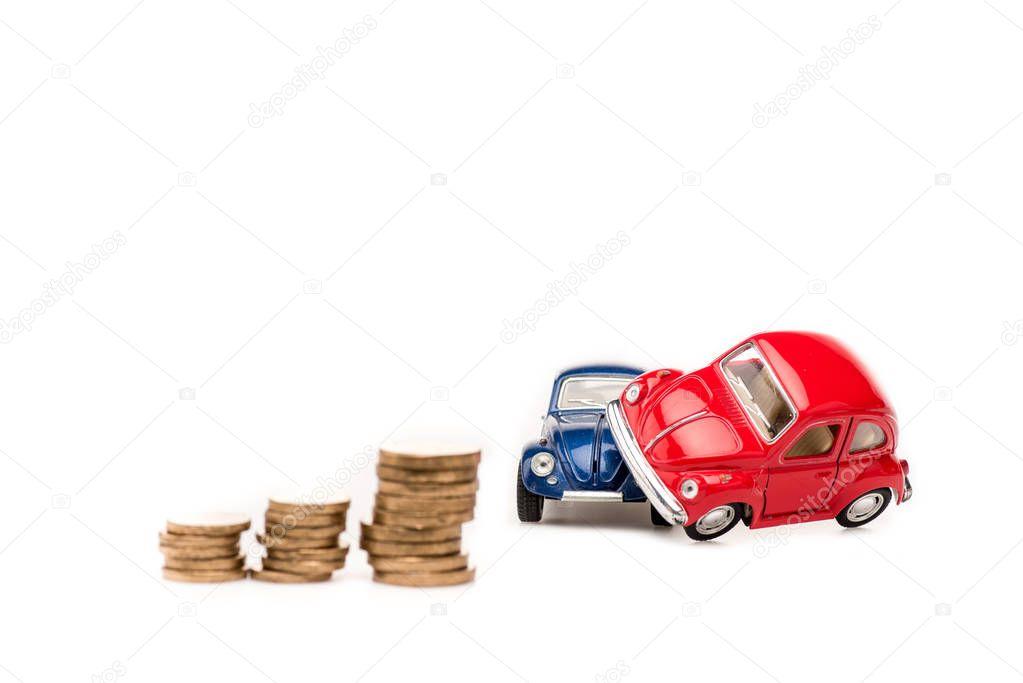 auto giocattolo rosse e blu e monete d'oro su bianco