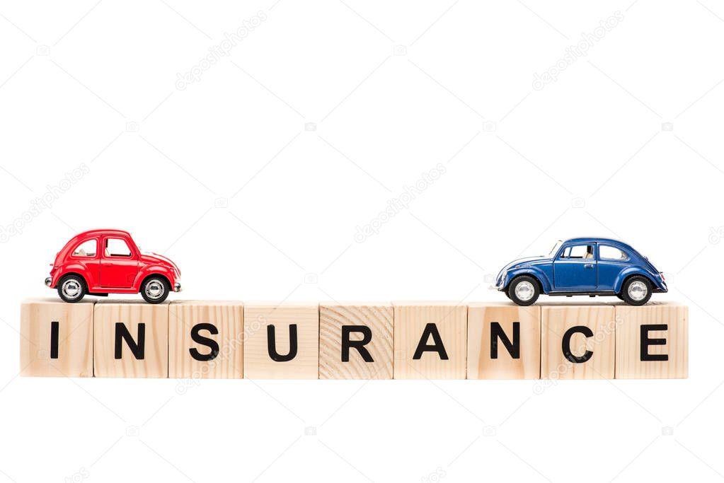 auto giocattolo blu e rosse su blocchi di legno con lettere isolate su bianco