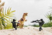 Photo toy soldiers aiming with guns at toy dinosaur on sand hill