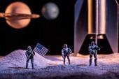 vojáci hraček držící americkou vlajku ve vesmíru blízko rakety a Planet