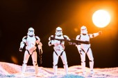 KYIV, UKRAINE - MAY 25, 2019: white imperial stormtroopers with guns on cosmic planet with sun on background