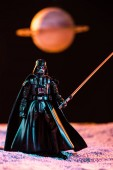 KYIV, UKRAINE - MAY 25, 2019: Darth Vader figurine with lightsaber with planet on background