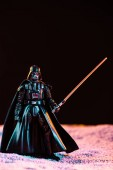 KYIV, UKRAINE - MAY 25, 2019: Darth Vader figurine with lightsaber isolated on black