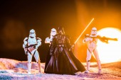 KYIV, UKRAINE - MAY 25, 2019: white imperial stormtroopers with guns and  Darth Vader with lightsaber on black background with bright sun