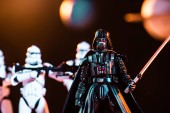 KYIV, UKRAINE - MAY 25, 2019: selective focus of Darth Vader with lightsaber and white imperial stormtroopers with guns on background