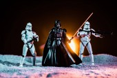 KYIV, UKRAINE - MAY 25, 2019: white imperial stormtroopers with guns and  Darth Vader with lightsaber on black background with sun