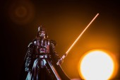 KYIV, UKRAINE - MAY 25, 2019: Darth Vader figurine with lightsaber on black background with shining sun