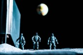 Photo toy soldiers standing in space on black background with planet earth