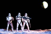 KYIV, UKRAINE - MAY 25, 2019: white imperial stormtroopers with guns in space on black background with planet Earth